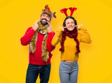 Couple Dressed Up For The Christmas Holidays Smiling With A Pleasant Expression While Pointing Mouth With Fingers On Yellow Background