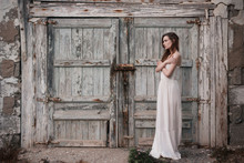 Side View Of Woman In White Dress Standing Near Wooden Barn Door