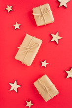 Some Christmas Presents In Decorative Box And Wooden Stars On A Red Background