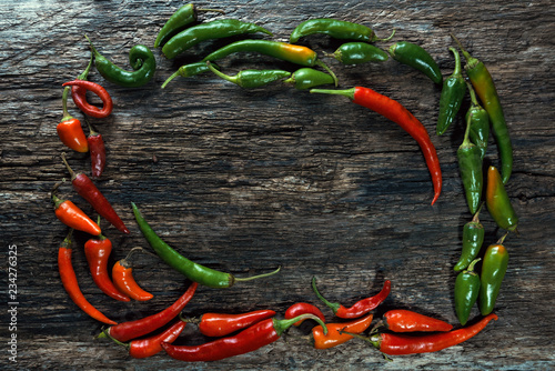 Tuinposter Kruiderij hot peppers on an old board/ Red and green hot peppers on an old wooden board