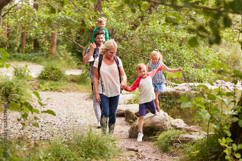 Fototapeta Family Hiking Along Path By River In UK Lake District
