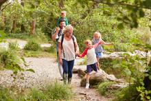 Family Hiking Along Path By Ri...