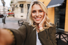 Image Of Charming Woman Smiling And Taking Selfie Photo, While Walking Through City Street