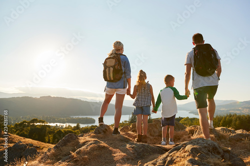 Fototapeta Rear View Of Family Standing At Top Of Hill On Hike Through Countryside In Lake