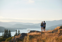 Rear View Of Couple Hugging On Top Of Hill On Hike Through Countryside In Lake District UK