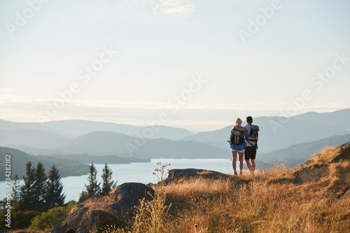 Fotografia Rear View Of Couple Hugging On Top Of Hill On Hike Through Countryside In Lake D