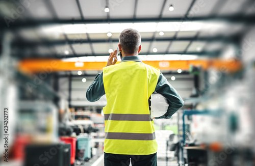 Pinturas sobre lienzo  A rear view of an industrial man engineer with smartphone in a factory, working