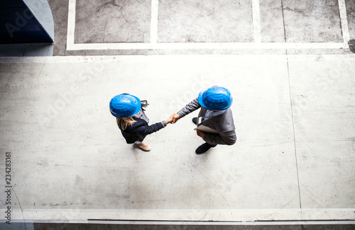 Fotografiet A top view of an industrial man and woman engineer in a factory, shaking hands