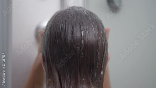 Stock Video of Young girl bathing under a shower at home - back view. Beautiful teen girl taking shower and washing in the bathroom. Happy child washing head, face and body with water. at Adobe Stock   Adobe Stock->