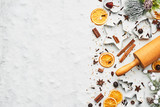 Fototapeta Dmuchawce - Holiday baking background for baking Christmas cookies with cutters, rolling pin and spices on white marble table covered with snow. Top view with copy space for text.
