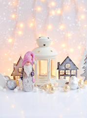 Christmas composition with lantern, gnome, toy houses, spruces and festive decorations. Christmas or New Year greeting card.