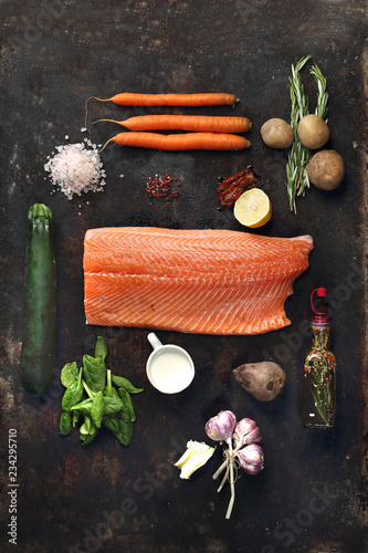 Fototapeta Łosoś, ryba z warzywami, etapy przygotowywania potrawy. Składniki potrawy, łosoś, cukinia, ziemniaki, marchew, buraki. Kompozycja na ciemnym tle. obraz