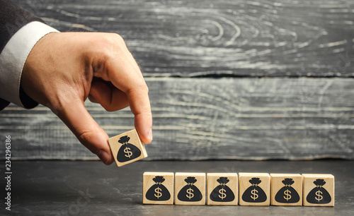 Fototapeta Businessman puts a block with a picture of dollars. The capital accumulation and successful business. Increased budget and profits in the team. Increase investment fund. Saving money. Economic boom obraz