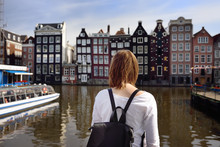 Young Woman Looking At The Famous Dancing Houses Of Amsterdam On Sunny Day