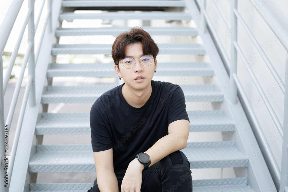 Fototapeta Handsome asian CASUAL glasses man sit on a staircase and smile posing on gray background.