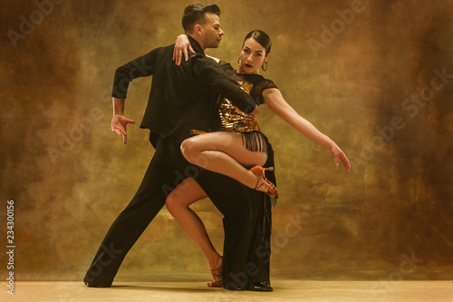 Fotografiet The young dance ballroom couple in gold dress dancing in sensual pose on studio background