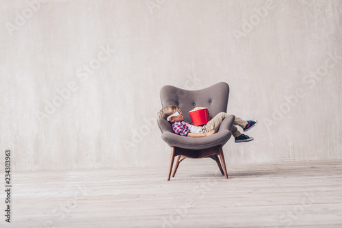 Sleeping little boy with popcorn in a chair