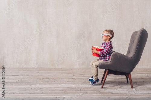 Little child in 3d glasses in a chair
