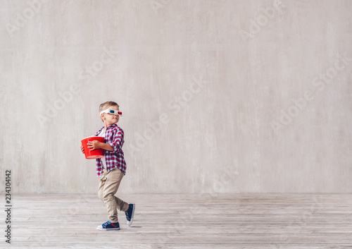 Little child in 3d glasses with popcorn