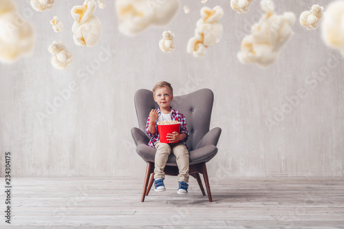 Little boy eating popcorn in a chair