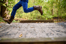 Boy Running Across A Small Footbridge, United States