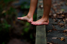 Close-up Of A Boy's Dirty Feet Standing On A Footbridge In The Forest, United States