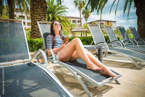 Fototapeta Woman on a lounger by the pool with mobile phone