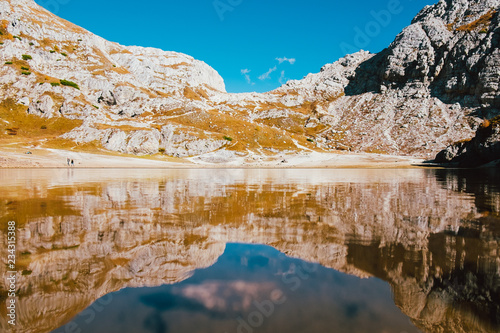 Fotografie, Obraz  perfectly symmetrical reflection in clean mountain lake in italian alps with cle
