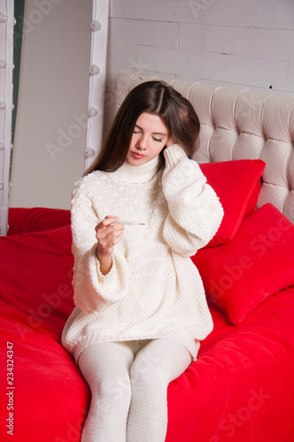 Fotografia  Sick woman sitting on the bed, looking at the thermometer