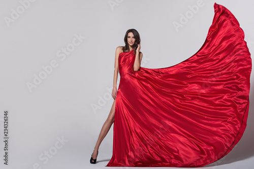 Foto  Beauty young woman in fluttering red dress. Gray background.