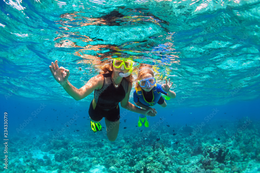 Fototapeta Happy family - mother, kid in snorkeling mask dive underwater with tropical fishes in coral reef sea pool. Show by hands divers sign OK. Travel lifestyle, beach adventure on summer holiday with child.