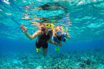 Sretna obitelj - majka, dijete u maski s ronjenjem roni pod vodom s tropskim ribama u bazenu s koraljnim grebenima. Pokažite rukama ronioci znak U redu. Putujte način života, avantura na plaži na ljetnom odmoru s djetetom.