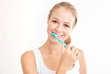 Beautiful Young Woman Brushing Her Teeth Against White Background