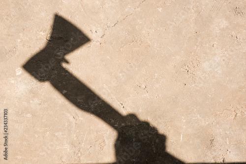 Fényképezés  Shadow of a hand with an ax on concrete