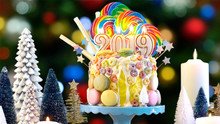 2019 Happy New Year's Candy Land Lollipop Drip Cake Against Bokeh Christmas Tree Lights.