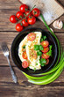 Omelet with cherry tomatoes and fresh green parsley in a black iron pan on a wooden background.