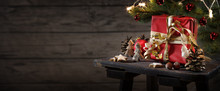 Red Christmas Gift Box And Decoration On An Small Table Against A Rustic Wooden Wall With Copy Space, Panoramic Format