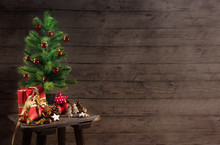 Artificial Christmas Tree With Red Baubles, Gift Box And Decoration On An Small Table In Front Of A Rustic Wooden Wall, Generous Copy Space