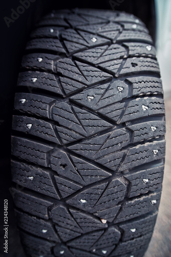 Fotografie, Obraz  Used snow tire with metal studs close up
