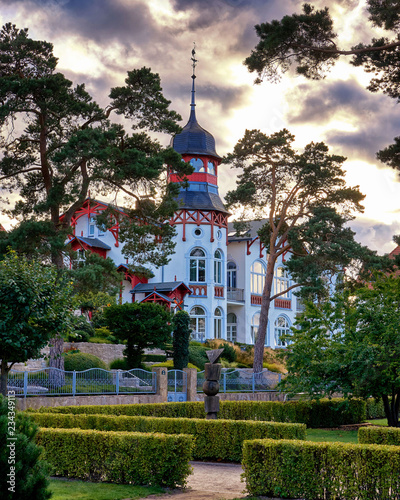 Obraz Park with old Baltic house with trees in the sunshine on the beach promenade Zinnowitz on the island of Usedom. - fototapety do salonu