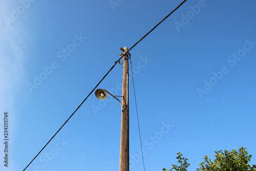 Fotografie, Obraz  Old street lamp post electricity pole wires wooden blue sky