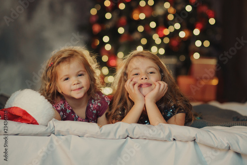 bac904454fc Two cute sisters in Santa Claus hats are sitting on a soft home bad against  the background of a festive Christmas tree hugging and ...