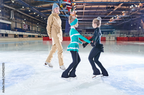 Full length portrait of two little girls figure skating and holding hands during practice in indoor rink