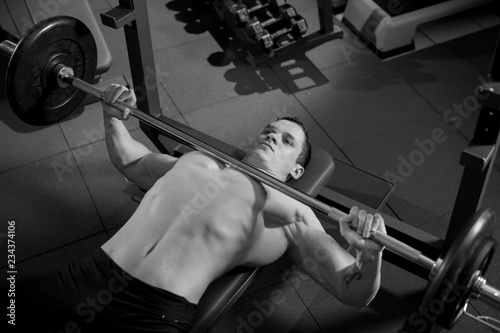 Foto op Canvas Paarden Brutal athletic man pumping up muscles on bench press