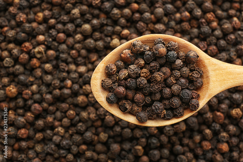 spoon-with-black-pepper-over-heap-of-grains-top-view