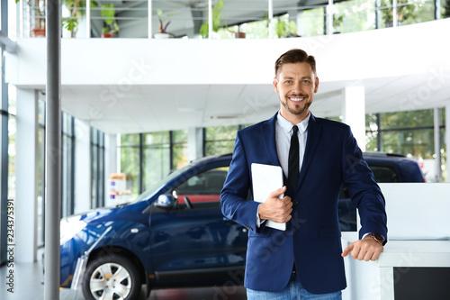 Fototapeta Salesman with tablet in modern car dealership obraz