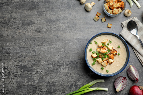 Flat lay composition with bowl of fresh homemade mushroom soup and space for text on gray background