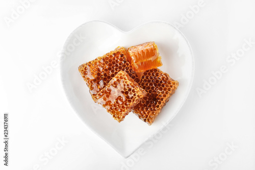 Heart shaped plate with honeycomb pieces isolated on white, top view