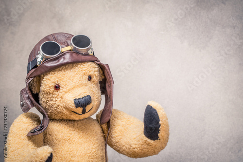 Photo Retro Teddy Bear toy in leather pilot's helmet with aviator goggles front textured concrete wall background