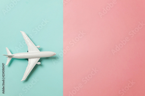 Fényképezés  Simply flat lay design miniature toy model plane on blue and pink pastel colorful paper trendy geometric background